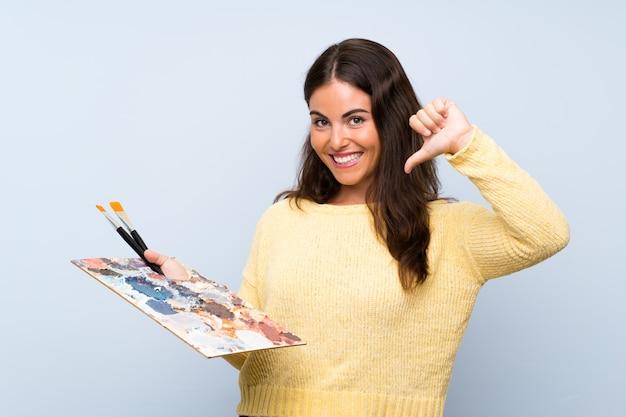 孤立した青い壁誇りと自己満足の上の若いアーティストの女性 Premium写真