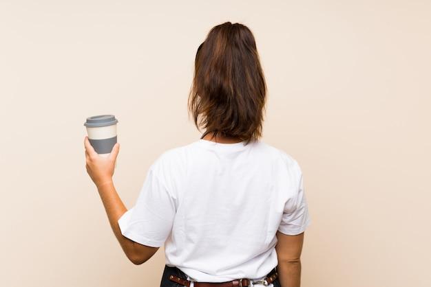 バックの位置でテイクアウェイコーヒーを保持している若い従業員の女性 Premium写真
