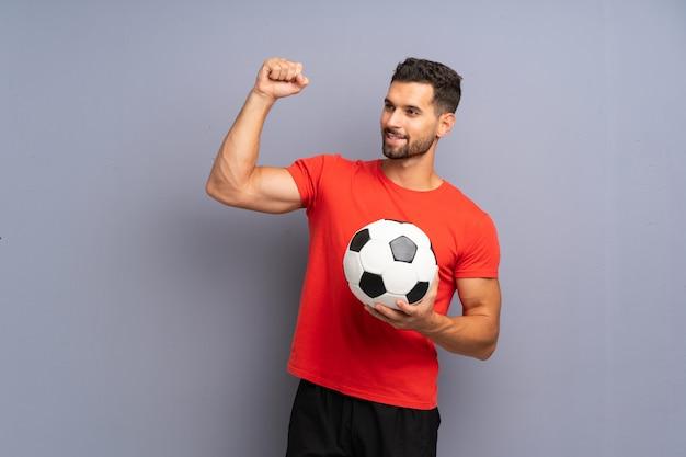 勝利を祝う孤立した白い壁の上のハンサムな若いフットボール選手男 Premium写真