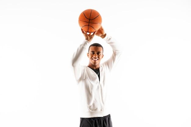 孤立した白い壁の上のアフロアメリカンバスケットボールプレーヤー男 Premium写真
