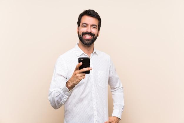Молодой человек с бородой держит мобильный телефон, отправив сообщение с мобильного телефона Premium Фотографии
