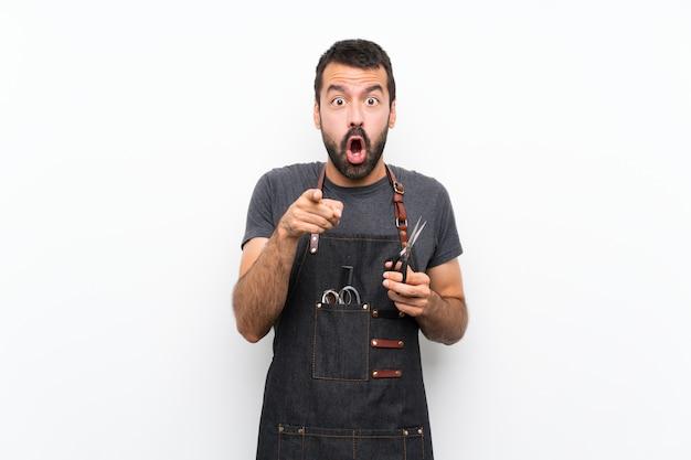 Мужской парикмахер в фартуке удивлен и указывает вперед Premium Фотографии