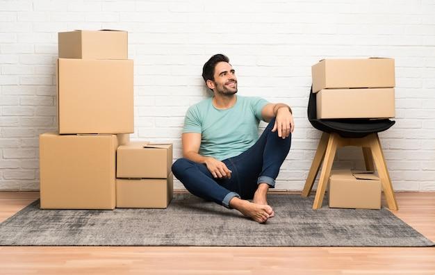 笑って見上げるボックスの間で新しい家に移動するハンサムな若い男 Premium写真
