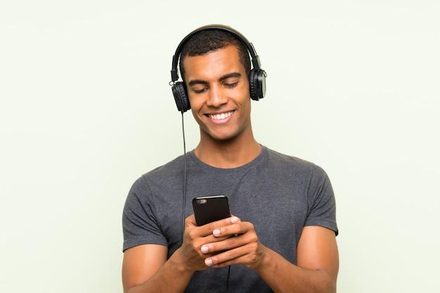 Молодой красавец прослушивания музыки с мобильного на изолированной зеленой стене Premium Фотографии