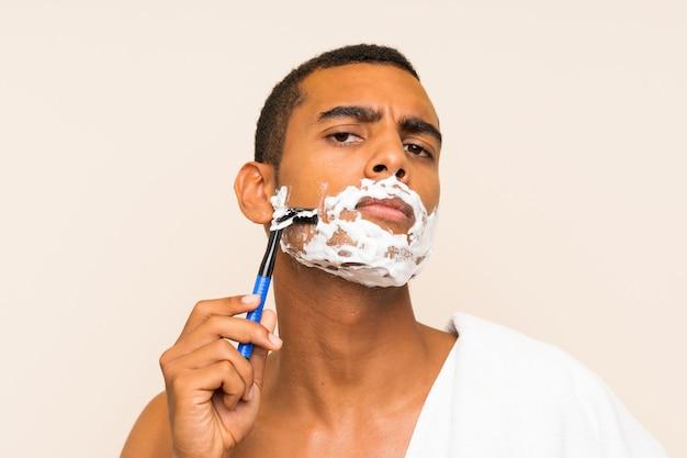 Молодой красавец брить бороду над изолированной стеной Premium Фотографии