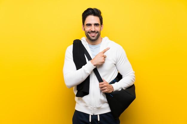 製品を提示する側を指している孤立した黄色の壁の上の若いスポーツ男 Premium写真