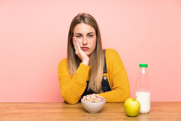 不幸で不満の穀物のボウルを持つ若い女性 Premium写真