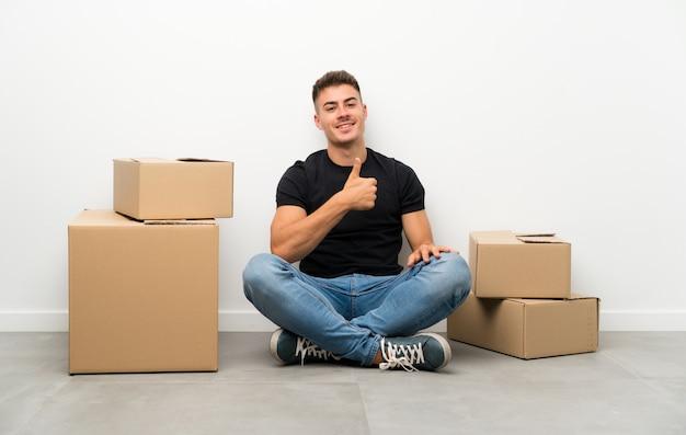 ハンサムな若い男がジェスチャーを親指を与えるボックスの間で新しい家に移動 Premium写真