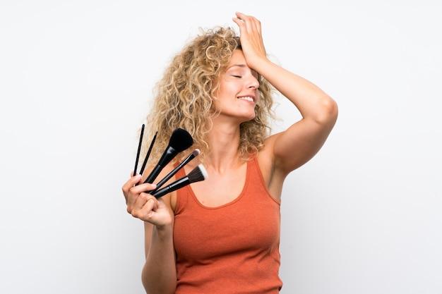 化粧ブラシの多くを保持している巻き毛の若いブロンドの女性は何かを実現し、解決策を意図しています Premium写真