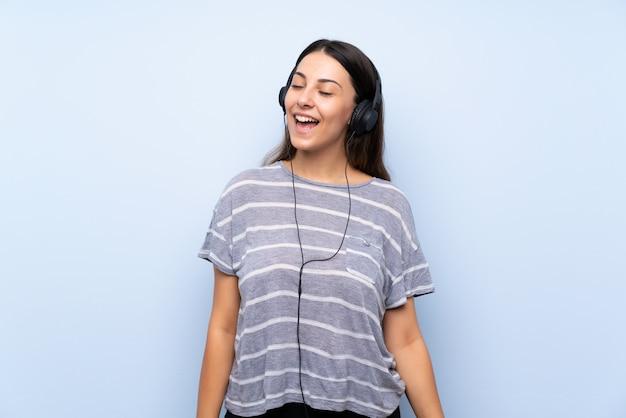 ヘッドフォンで音楽を聴く青い壁の上の若いブルネットの女性 Premium写真
