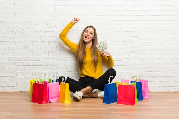 たくさんのお金を取って買い物袋の多くを持つ若い女の子 Premium写真