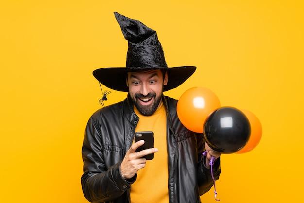 Человек с шляпой ведьмы держит черные и оранжевые воздушные шарики для хэллоуина удивлен и отправив сообщение Premium Фотографии