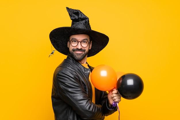 メガネとハロウィーンパーティーの黒とオレンジの気球を押しながら笑みを浮かべてウィッチハットを持つ男 Premium写真