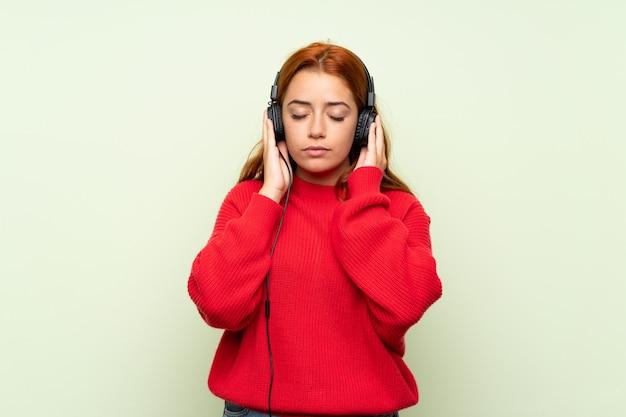 ヘッドフォンで音楽を聴く孤立した緑の壁の上のセーターとティーンエイジャーの赤毛の女の子 Premium写真