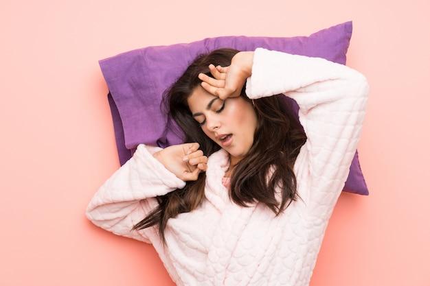 Девушка-подросток в халате на розовом фоне и зевая Premium Фотографии