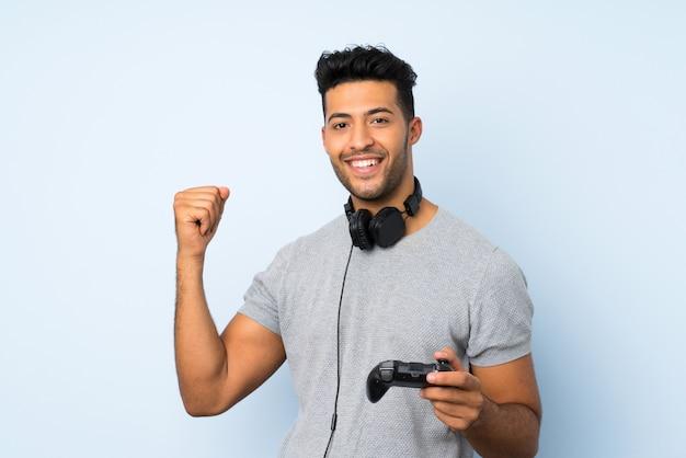 ビデオゲームで遊ぶ孤立した壁の上の若いハンサムな男 Premium写真
