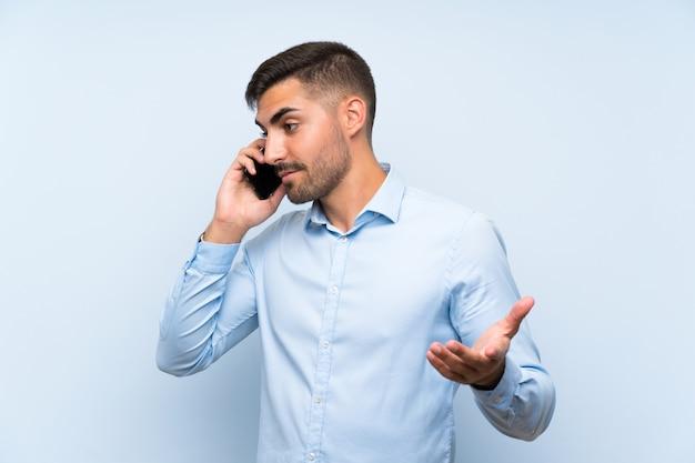 勝利の位置に電話で孤立した白い壁に金髪の男 Premium写真
