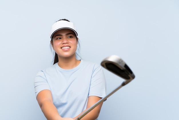 孤立した青い壁の上の若いゴルファーアジアの女の子 Premium写真