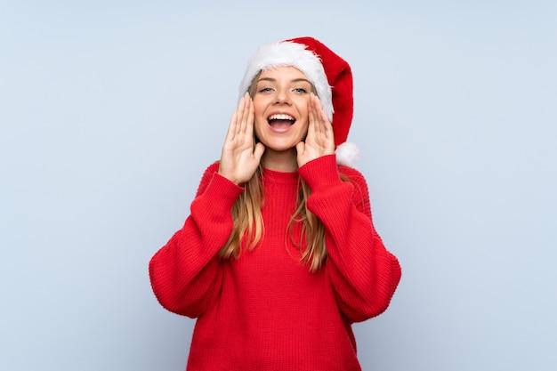 クリスマス帽子と青い背景上で叫んでいる女の子 Premium写真