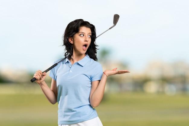 屋外で驚きの表情を持つ若いゴルファーの女性 Premium写真