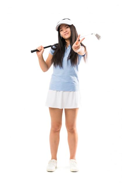 若いアジアのゴルファーの女の子笑顔と勝利のサインを示す Premium写真