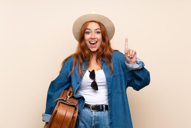 素晴らしいアイデアを指しているスーツケースで赤毛の旅行者の女の子 Premium写真