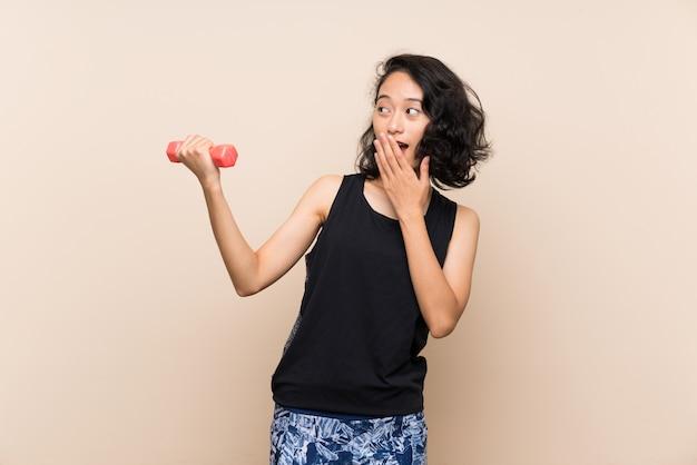 驚きとショックを受けた表情で重量挙げを作る若いアジアの女の子 Premium写真