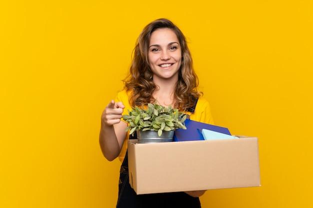 Молодая белокурая девушка делая движение пока поднимающ коробку полный вещей удивленных и указывающих фронт Premium Фотографии