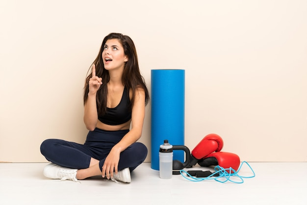 指を上向きのアイデアを考えて床に座ってティーンエイジャーのスポーツ少女 Premium写真