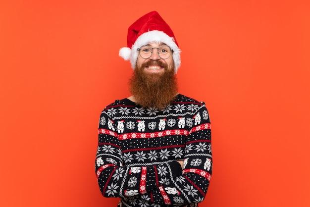 Рождественский человек с длинной бородой над изолированной красной стеной много улыбается Premium Фотографии