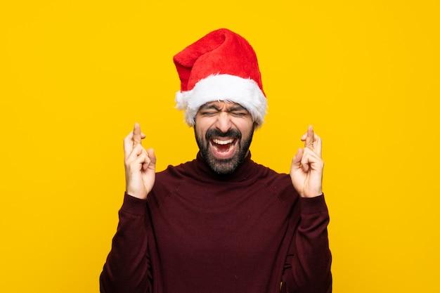 指を交差で分離された黄色の壁を越えてクリスマス帽子の男 Premium写真