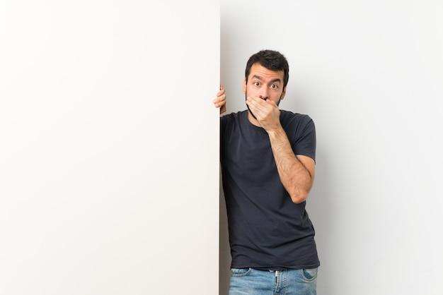 手で口を覆っている大きな空のプラカードを保持しているひげの若いハンサムな男 Premium写真