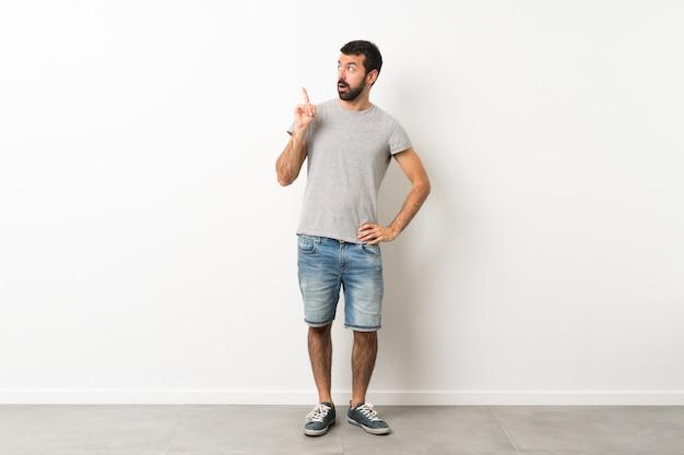 指を上向きにするアイデアを考えてひげを持つハンサムな男の全身ショット Premium写真