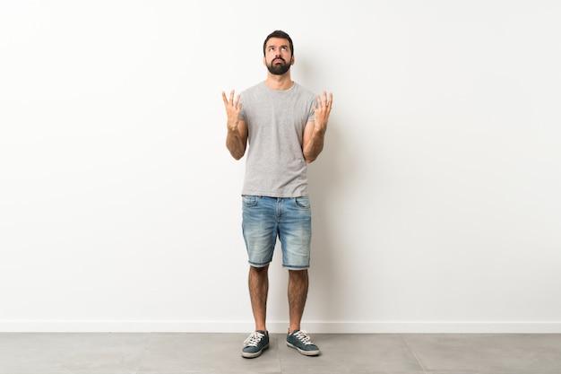 悪い状況にイライラしたひげを持つハンサムな男の全身ショット Premium写真