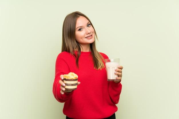 牛乳とマフィンのガラスを保持しているティーンエイジャーの女の子 Premium写真