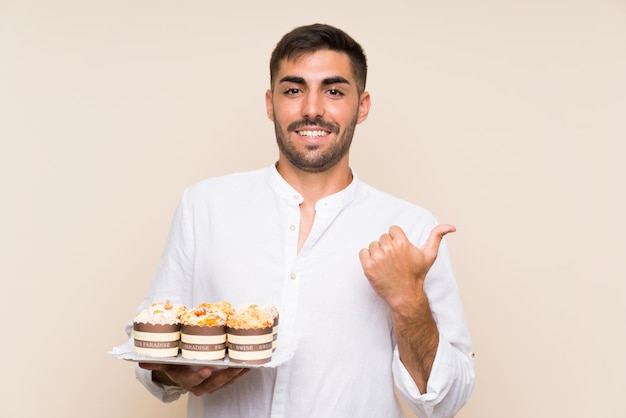 側を指しているマフィンケーキを持ってハンサムな男 Premium写真