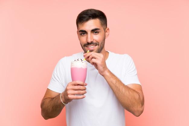 Молодой человек с клубничным молочным коктейлем Premium Фотографии