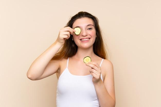 キュウリのスライスを保持している若いブルネットの少女 Premium写真