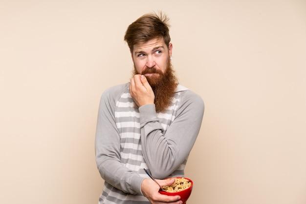 Рыжий мужчина с длинной бородой держит миску каши и мышления Premium Фотографии
