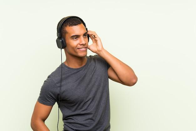携帯電話で音楽を聴く若いハンサムな男 Premium写真
