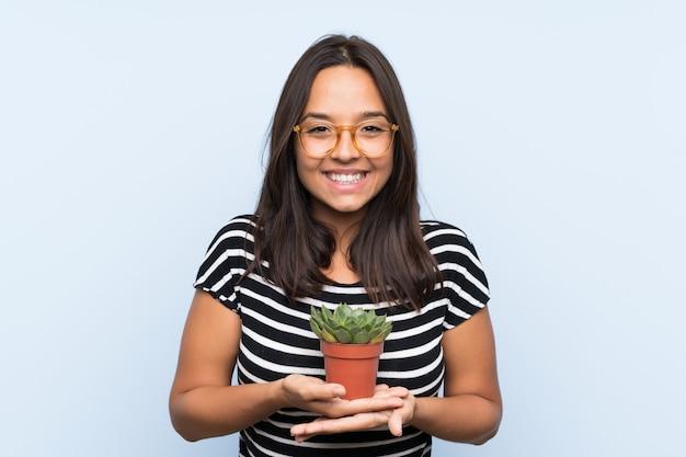 植物を保持している若いブルネットの女性 Premium写真