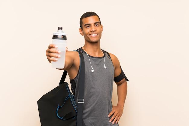 水のボトルと孤立した背景の上のスポーツ男 Premium写真