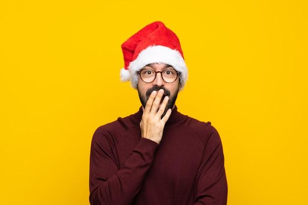 Человек с шляпой рождества над изолированной желтой стеной с стеклами и удивленный Premium Фотографии