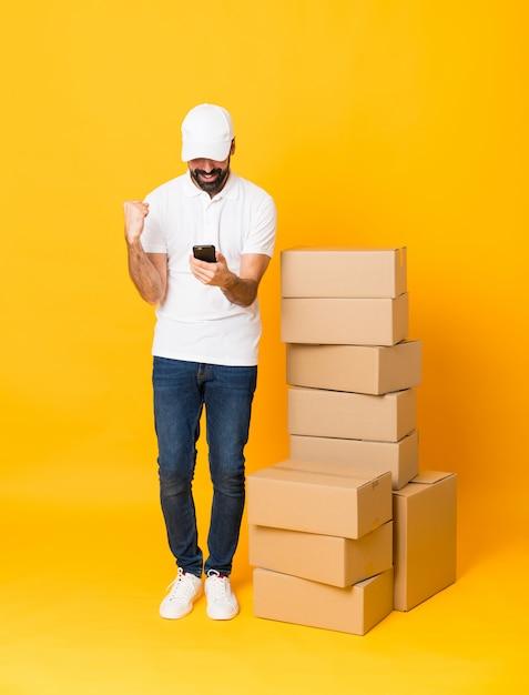 Полная длина доставщик среди коробок на изолированной желтой стене удивлен и отправив сообщение Premium Фотографии