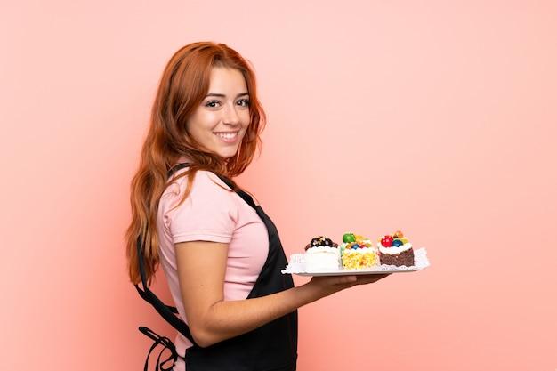 Рыжая девушка подросток держит много различных мини-пирожных над розовой стеной, улыбаясь много Premium Фотографии