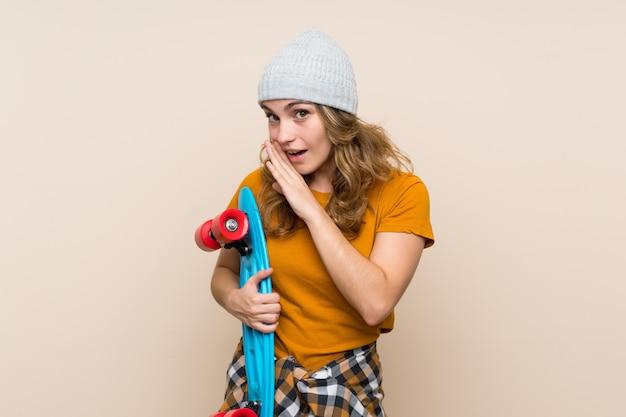 Девушка молодого конькобежца белокурая над изолированной стеной шепча что-то Premium Фотографии