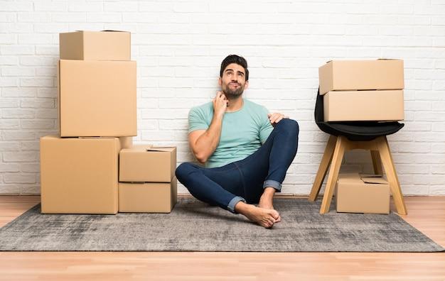 アイデアを考えてボックス間で新しい家に移動するハンサムな若い男 Premium写真