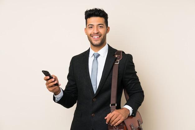 孤立した壁の上の若いハンサムな実業家男 Premium写真
