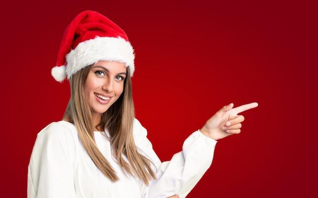 Девушка с шляпой рождества над изолированной стеной указывая палец в сторону Premium Фотографии