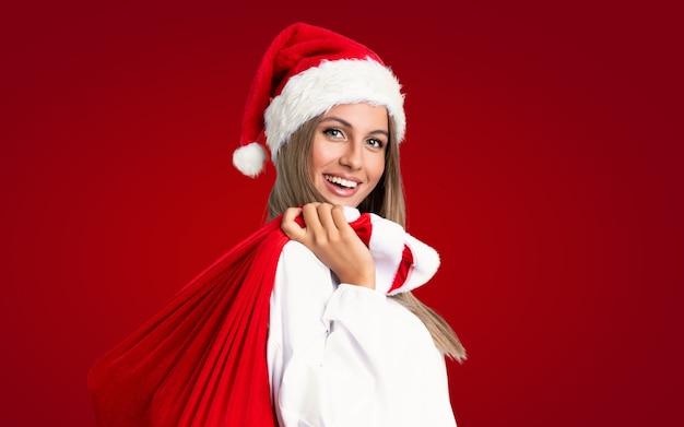 クリスマス休暇で孤立した赤い壁の上のプレゼントの完全な袋を拾う若いブロンドの女性 Premium写真